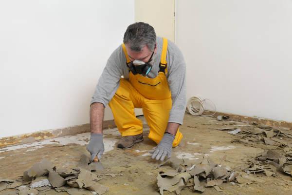 Mann bearbeitet Fußboden mit Atemmaske